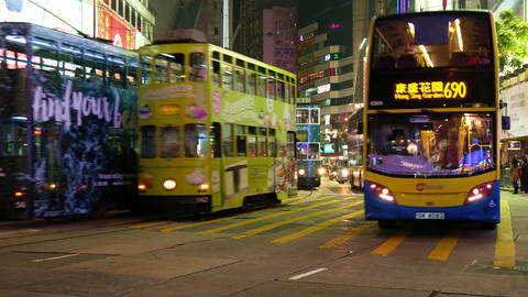 Trams and buses move along a busy road on Hong Kong island in the evening Footage