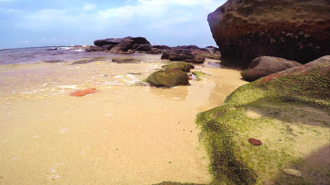 Gentle waves breaking on a white sandy beach with rocks in the foreground Footage
