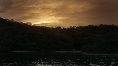 Gorgeous view from the ocean of island back lit by a sunset sky Footage