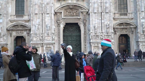 Man taking picture to a lady feeding the pigeons in Duomo Square of Milan Italy Footage