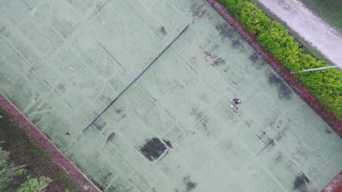 Birds eye Aerial of man playing free style football tricks on a tennis court Footage