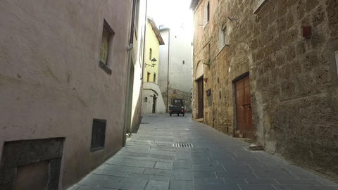 Italian Piaggio Ape tricycle driving in a narrow street in Umbria Italy Footage