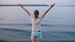 BackView of Young Lady Raising Hands Celebrating Nice Summer Evening near Lake Footage