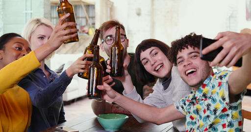 Group of friends posing for a group selfie with beer bottles Live Action