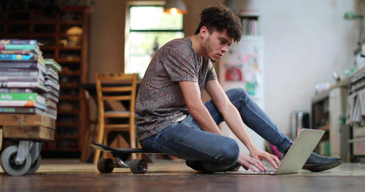 Young adult male sitting on skateboard using laptop Live Action