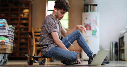 Young adult male sitting on skateboard using laptop Footage