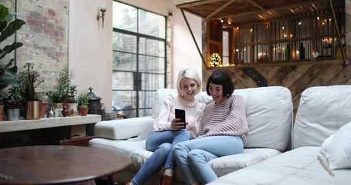 Young adult female friends looking at smartphone at home ビデオ