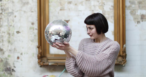 Young adult female looking at her reflection in disco ball Footage