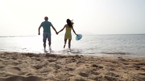 Active couple running on a yellow sandy beach with blue sky and sea on the Footage
