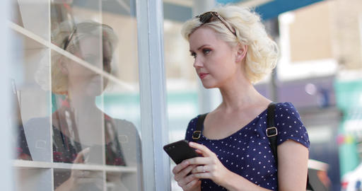 Young adult female using a smartphone whilst shopping Live Action