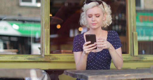 Young adult female using smartphone in bar Footage