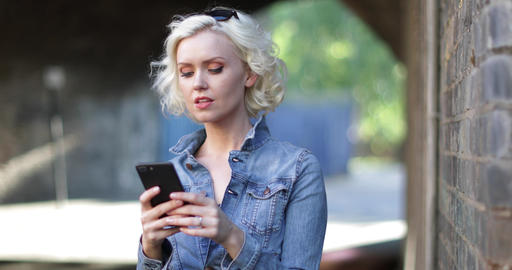 Young adult female using smartphone on street ビデオ