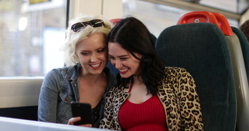 Young adult female friends travelling on train looking at smartphone Live Action