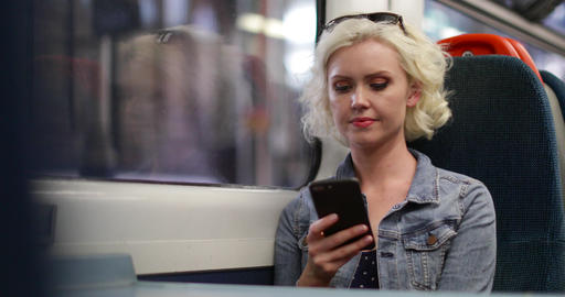 Young adult female travelling on train looking at smartphone Live Action