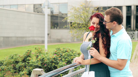 The man made a surprise to a beautiful girl by giving her a flower, a red rose Footage