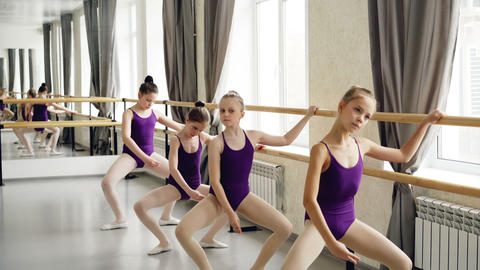 Small girls starting ballet-dancers in leotards are doing exercises holding Footage