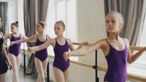 Cute little girls are having choreography class doing exercises at ballet bar Footage