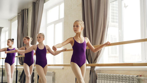 Starting ballet-dancers are doing exercises at ballet barre in spacious ballroom Footage