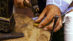 Man works with hammer and anvil coppersmith bracelet historical reconstruction GIF