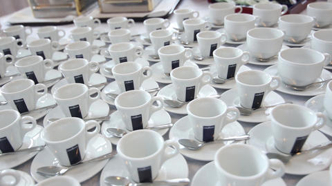 In the restaurant on a table stand white cups and saucers ranked. Many cups GIF