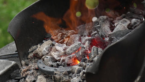 Blacksmith corrects coals in a Brazier and harassing fire from the Horseshoe Footage