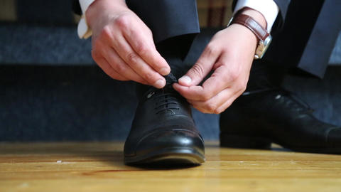 Man ties the laces on black shoes. Close-up of hands and shoes GIF