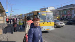 Passengers go out and get on the yellow city public bus at bus stop on city road Footage