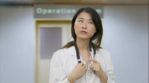 Asian female doctor in hospital operation room thinking and has breakthrough ビデオ