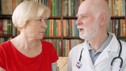 Male professional doctor at work. Senior physician consulting sick patient at Footage