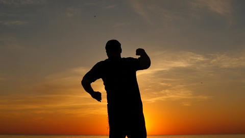 aged man expressing joy with hand up at sunset slow motion silhouette Footage