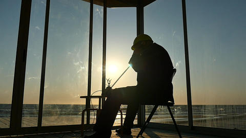 Man in helmet speak by regular phone in house near sea beach silhouette 영상물