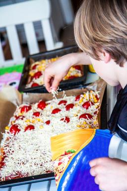 Happy little boy preparing pizza フォト