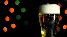 A glass of cold beer on a black background. HD Footage