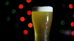 A glass of cold beer on a black background with colored lights. Beer is foaming Footage