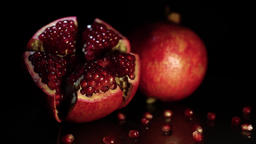 Two fruit pomegranates rotate on a black table on a black background. HD Footage