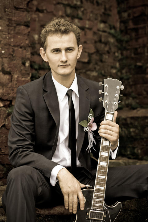 Young handsome groom sitting and holding a guitar, vintage, black and white フォト