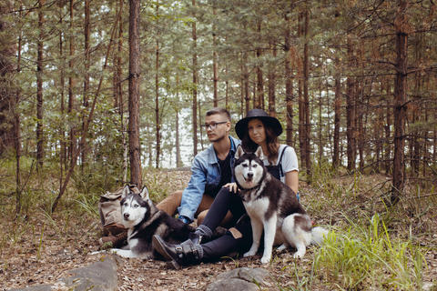 Young couple with dogs in forest フォト