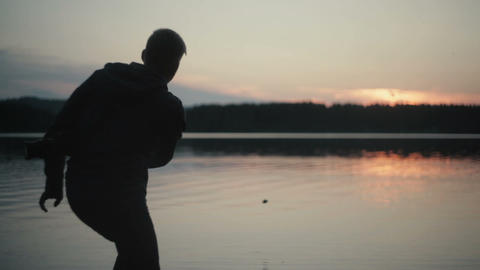 silhouette man throwing stones at the lake sunset Footage