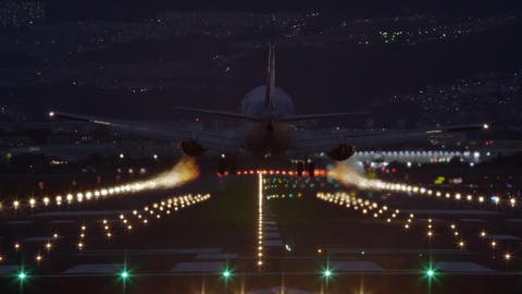 Airliner landing on the runway at night - back view Footage