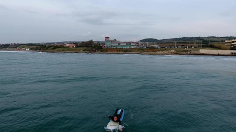 Amazing aerial orbit around surfers while paddling in the ocean at sunset ビデオ