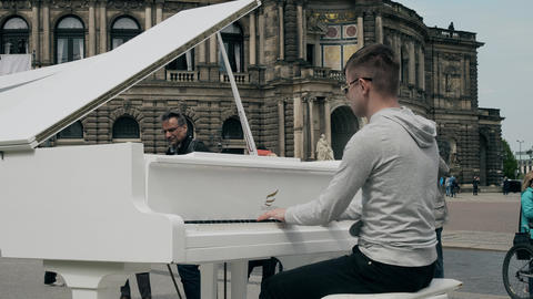 DRESDEN, GERMANY - MAY 2, 2018. Young man playing grand piano in historic centre 영상물