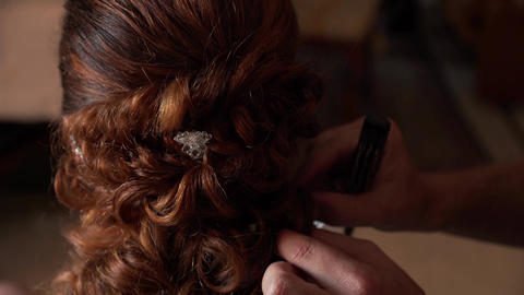 Close-up of a stylist brides her hair at a wedding 영상물