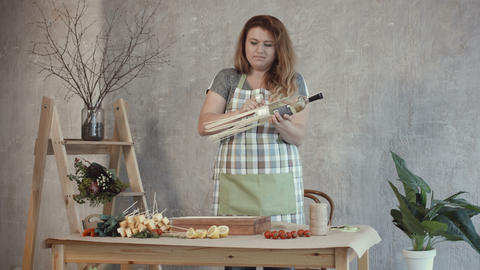Redhead woman arranging edible bouquet at workplace Footage