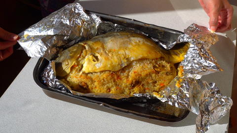 female hands unfolding of baked fish in foil フォト