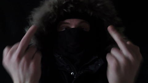the masked robber shows to the camera the finger フォト