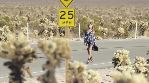 woman walks along an empty road overlooking the cacti Live Action