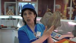 Saleswoman shows dried salted flatfish at fish market ビデオ