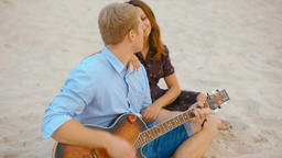 Young Family is sitting on Sand on Beach Playing Guitar and Singing in Summer Footage