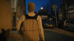 Young Guy with a Backpack is Walking in a Dark Street with his Phone at night Footage