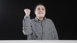 Young excited feminist shows success, victory, yes gesture, black background Footage
